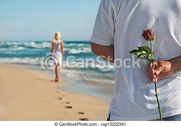 loving couple, man with rose waiting his woman on the sea beach at summer, the romantic, wedding or valentines day concept - csp13222341