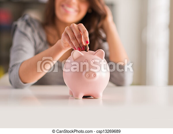 Woman Putting Coin In Piggy Bank - csp13269689