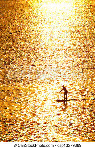 paddleboarding in sunset - csp13279869