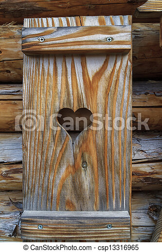 Window shutter with heart of a wooden log cabin in the European Alps - csp13316965