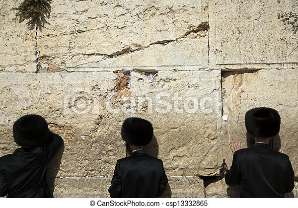 Three orthodox Jewish young adult pressed in prayer against the wailing wall in the old city of Jerusalem.