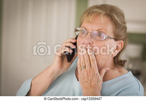 Shocked Senior Adult Woman on Cell Phone in Kitchen - csp13359447