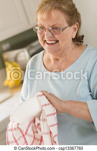 Senior Adult Woman Drying Bowl At Sink in Kitchen - csp13367760