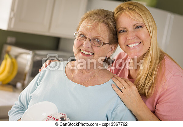 Senior Adult Woman and Young Daughter Portrait in Kitchen - csp13367762