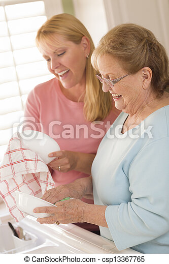 Senior Adult Woman and Young Daughter Talking in Kitchen - csp13367765