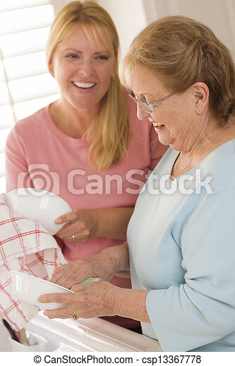 Senior Adult Woman and Young Daughter Talking in Kitchen - csp13367778