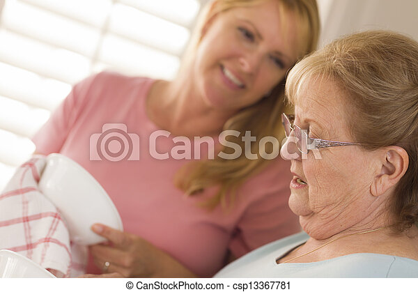 Senior Adult Woman and Young Daughter Talking in Kitchen - csp13367781