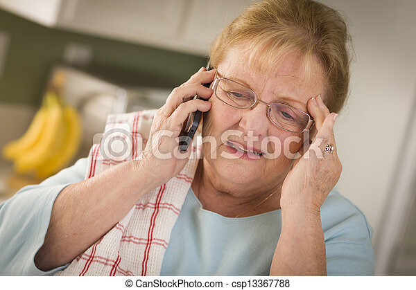 Shocked Senior Adult Woman on Cell Phone in Kitchen - csp13367788