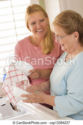 Senior Adult Woman and Young Daughter Talking in Kitchen - csp13384237
