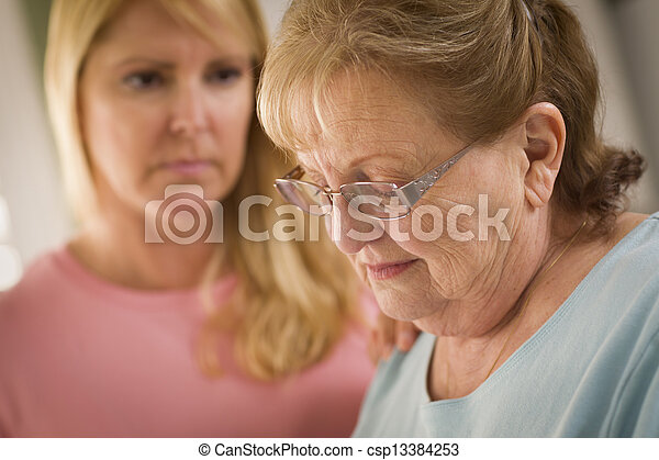Young Woman Consoles Senior Adult Female - csp13384253