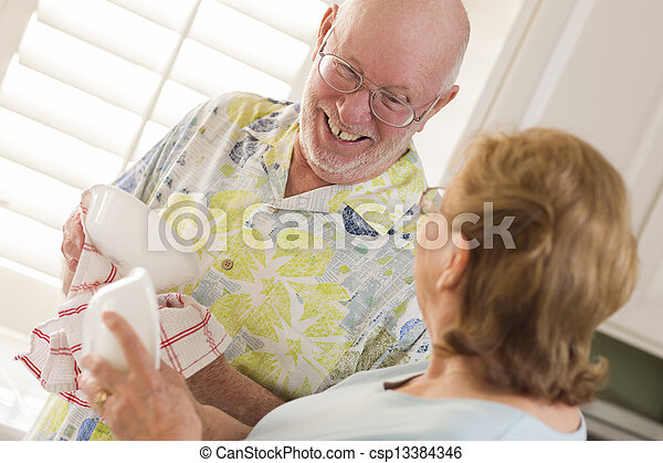 Senior Adult Couple Washing Dishes Together Inside Kitchen - csp13384346