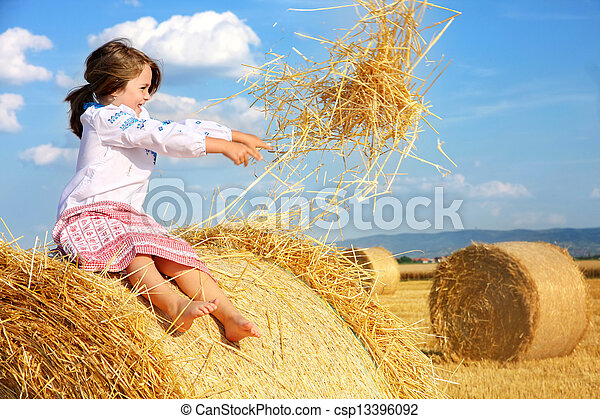 small rural girl on harvest field with straw bales - csp13396092