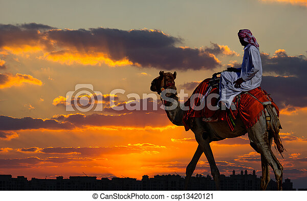 Bedouin on a camel in the desert and a modern city on the horizon - csp13420121