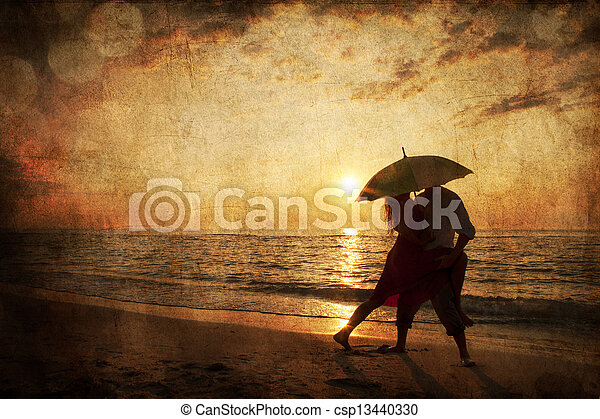 Couple kissing under umbrella at the beach in sunset. Photo in old image style. - csp13440330
