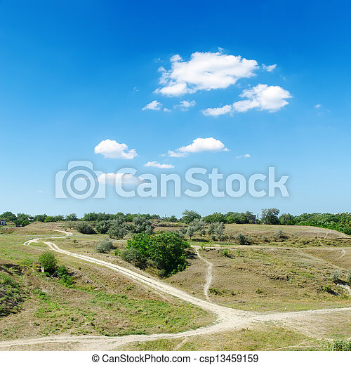 hill to river with trails under blue sky with clouds - csp13459159