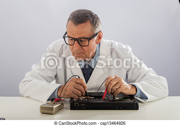 Senior Technician With Glasses, Repairing Computer - csp13464926