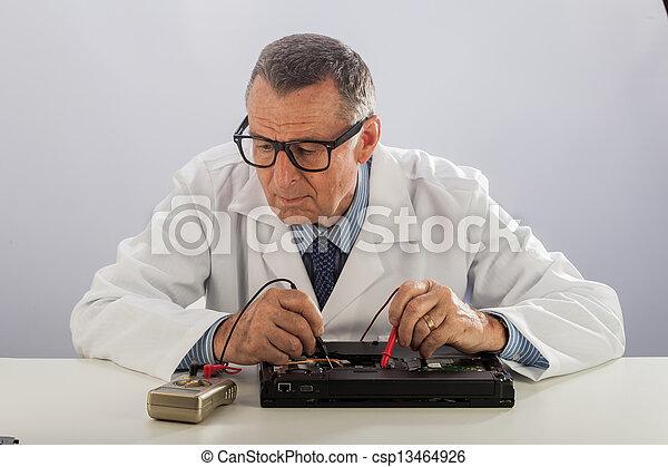 Senior Technician With Glasses, Repairing Computer - csp13464926