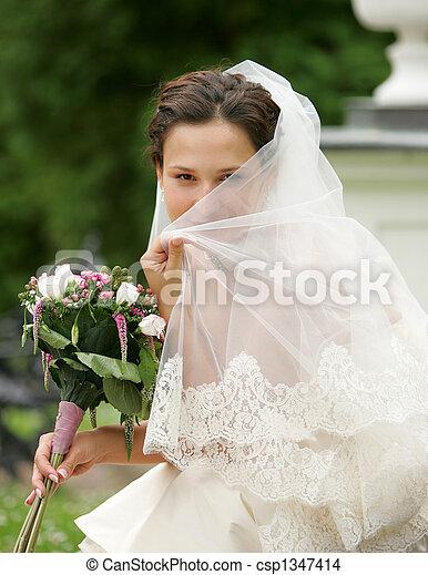 Bride hiding behind her veil - csp1347414