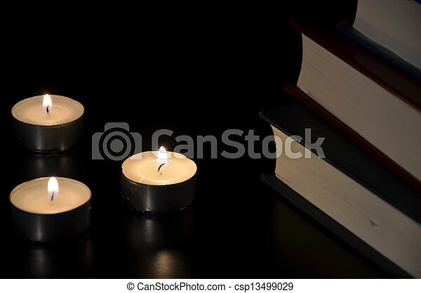 Three burning candles and old book in the dark