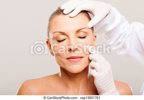 doctor examining mid age woman skin - csp13501761