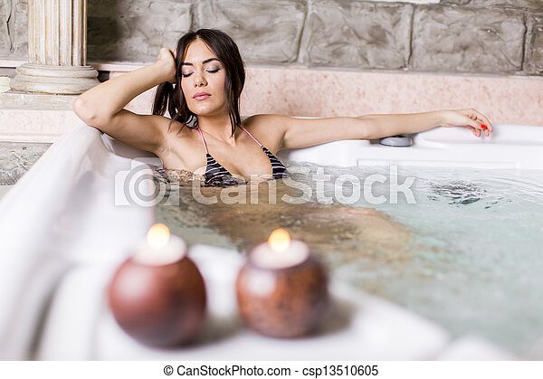 Pretty young woman relaxing in the hot tub - csp13510605