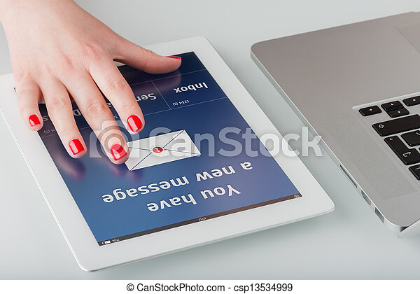 Woman's hand with red manicure opens a new email message on a tablet computer. - csp13534999