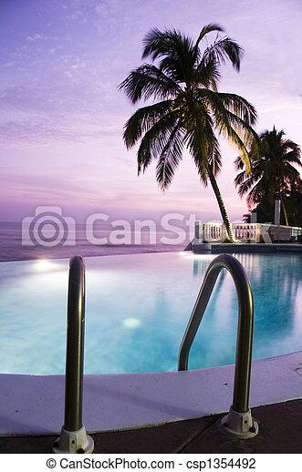 luxury infinity swimming pool caribbean sunset - csp1354492
