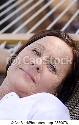 Portrait beautiful mature woman sleeping, with smiling happy and relaxed but sad facial expression, contemplating.