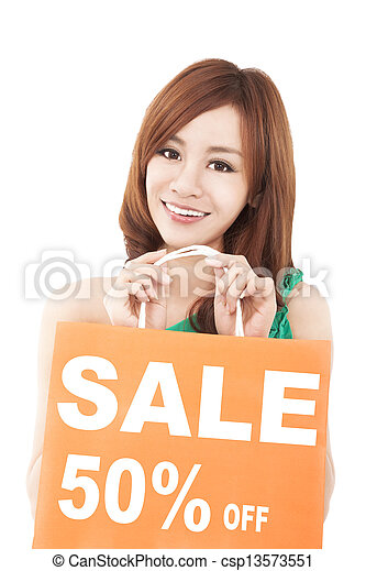 happy  woman showing shopping bag with sale written - csp13573551