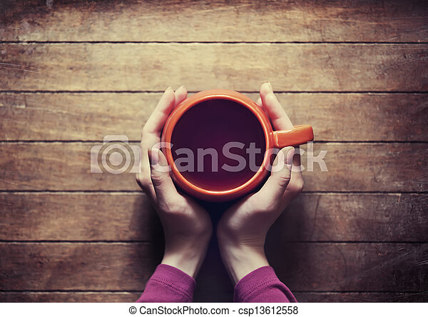 woman holding hot cup of tea - csp13612558
