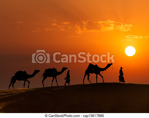 Rajasthan travel background - two indian cameleers (camel drivers) with camels silhouettes in dunes of Thar desert on sunset. Jaisalmer, Rajasthan, India - csp13617866
