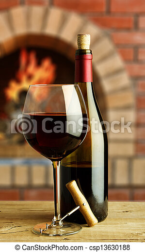 bottle and glass of red wine on the background of the rural fireplace - csp13630188