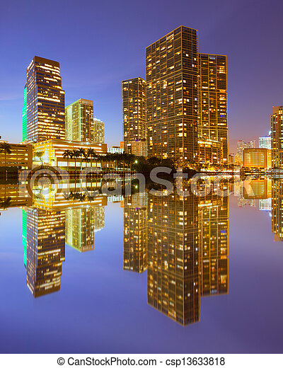 City of Miami Florida, night skyline. Cityscape of residential and business buildings lit by bright lights after sunset with reflections - csp13633818
