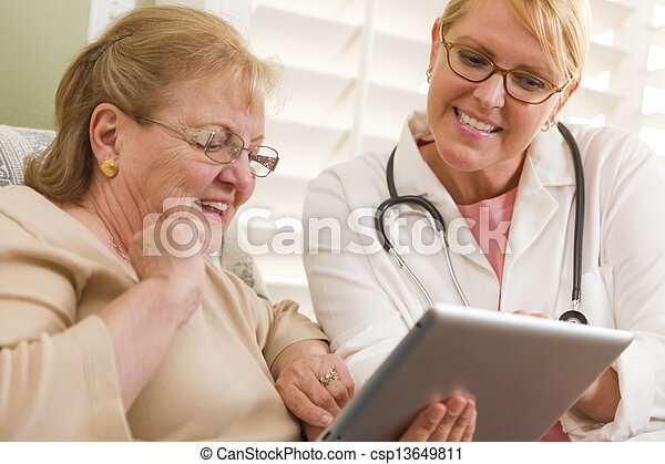 Doctor or Nurse Talking to Senior Woman with Touch Pad - csp13649811