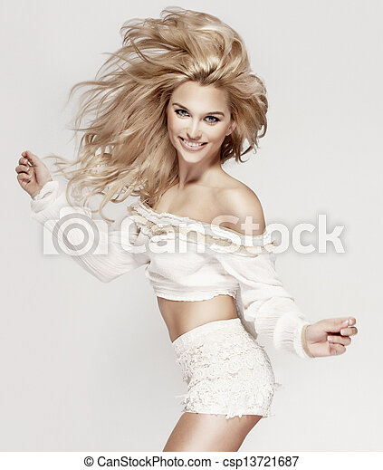 Fashionable blonde smiling lady jumping, looking at camera. - csp13721687