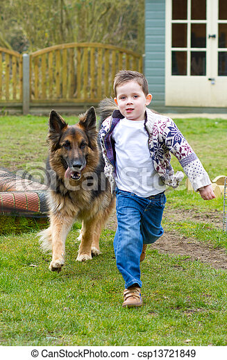 little boy running with his pet german shepherd