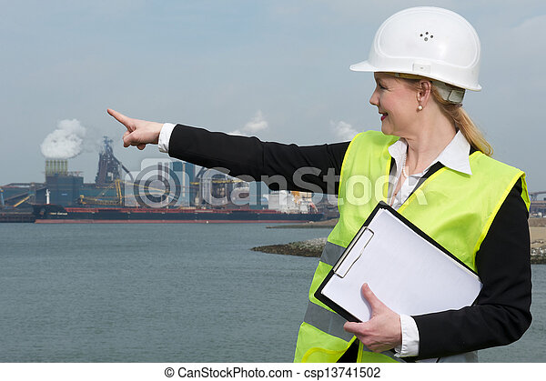 Female inspector in hardhat and safety vest pointing at industrial site - csp13741502
