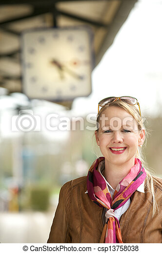 Beautiful mature woman smiling under train station clock - csp13758038