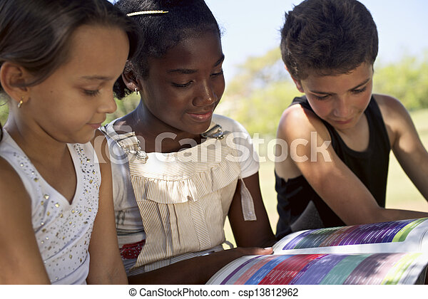 Children and education, kids and girls reading book in park - csp13812962