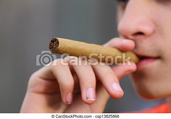Stock Image of Underage Smoking - An underage young man putting a ...