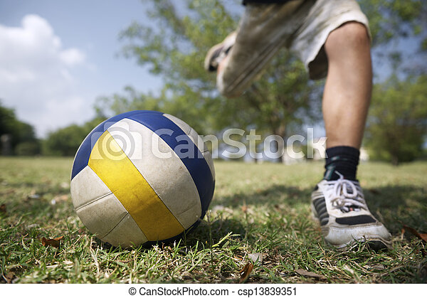Kids playing soccer game, young boy hitting ball in park - csp13839351