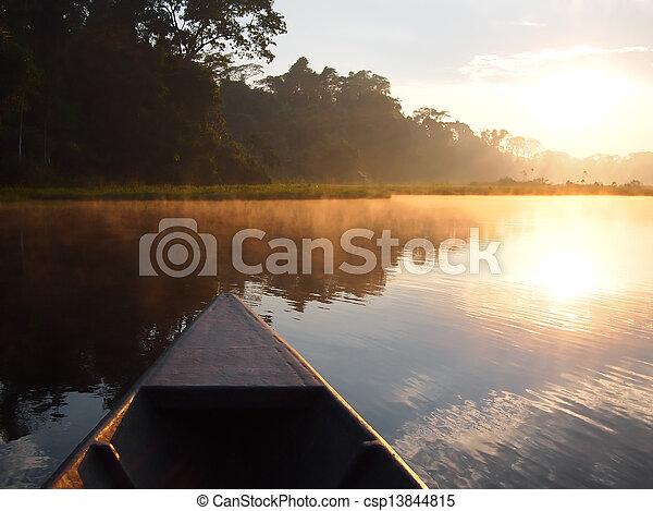 Amazon rainforest sunrise by boat - csp13844815