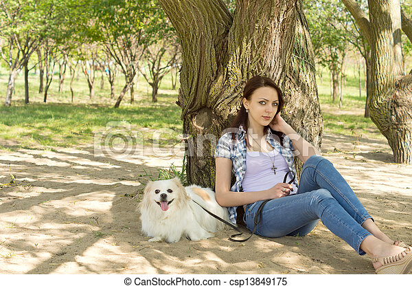 Little dog and its owner resting in the shade