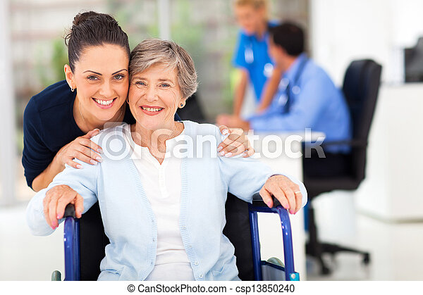 adult daughter accompanying senior mother visiting doctor - csp13850240