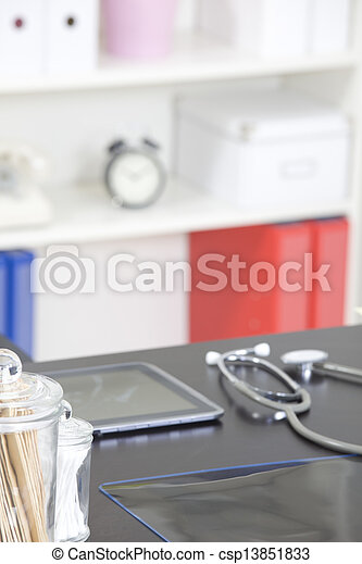 Doctor's office desk with medical supplies documents stethoscope - csp13851833