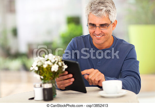 middle aged man surfing the internet using tablet computer - csp13852413