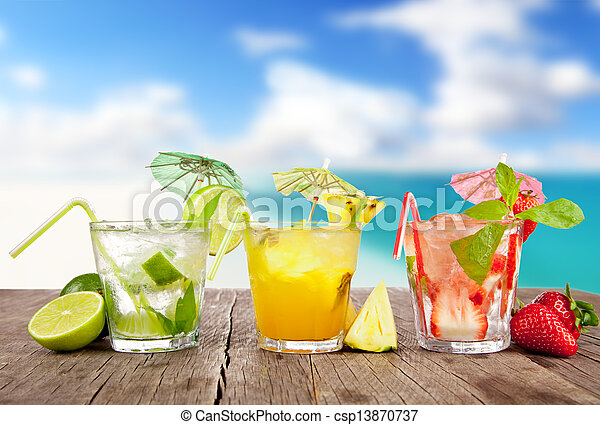 Summer cocktails with pieces of fruit on wooden table. Blur beach on background - csp13870737
