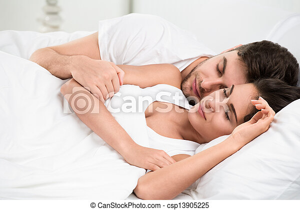 Young adult couple sleeping in bedroom - csp13905225