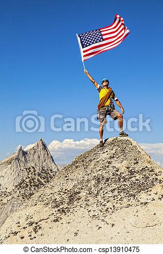 Climber waves flag on mountain peak. - csp13910475