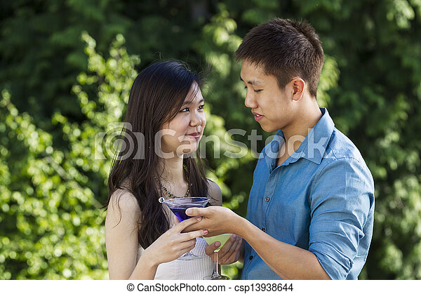 Young Adult Couple Sharing Drinks Outdoors - csp13938644